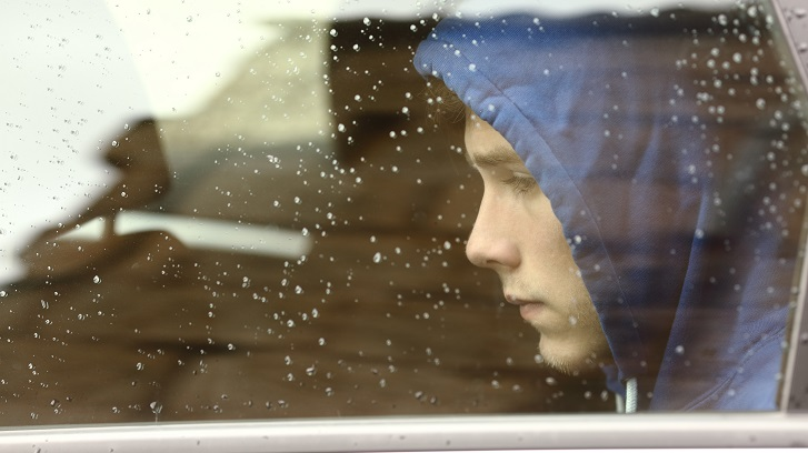Sad teenager boy worried inside a car looking through the window